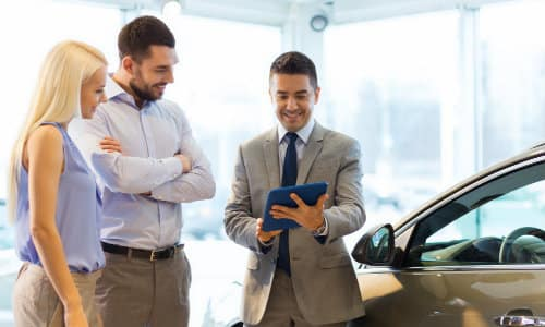 a salesman helping a couple shop for their new car showing rates on a tablet inside a dealership