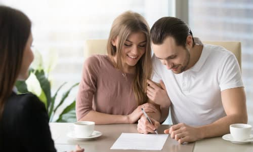 a couple signing a finance or lease contract for a new car purchase at an automotive dealership