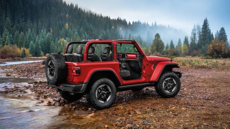 2020 Jeep Wrangler exterior side shot with firecracker red paint color and doors removed on wet earth and wood chips near a lake and forest with a foggy sky