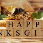 Happy Thanksgiving written out in wooden blocks near a cornucopia of leaves, nuts, corn, vegetables, and other autumn and fall assortments