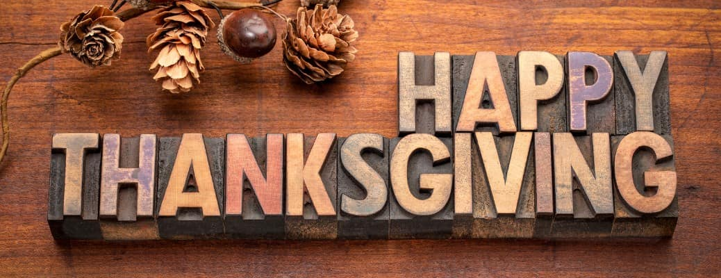 Happy Thanksgiving header in letter block on a wooden table near ornamental acorns and pinecones