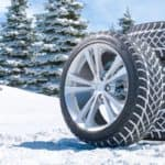 a pile of tires with their tread lined with snow sitting out near sheets of white snow and an evergreen tree forest