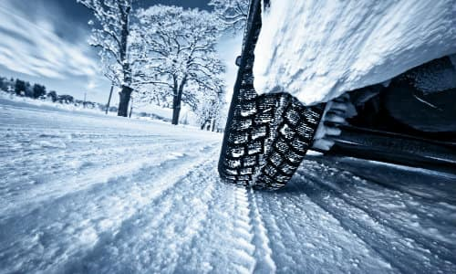 a tire driving on a snowy winter road as it leaves its tread marks on freshly fallen snow