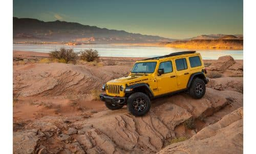 2020 Jeep Wrangler Rubicon EcoDiesel exterior shot with yellow gold paint color parked on a desert rock plain near a lake and mountains
