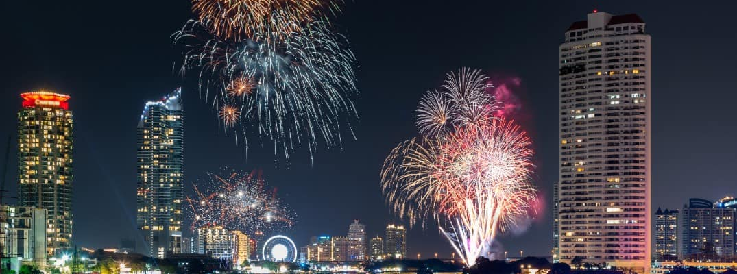 a city skyline at night lit up with lights and exploding fireworks in the sky for a new year's eve celebration