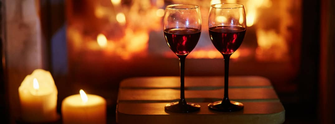 a couple of glasses of red wine set on a stool near lit candles and a fireplace