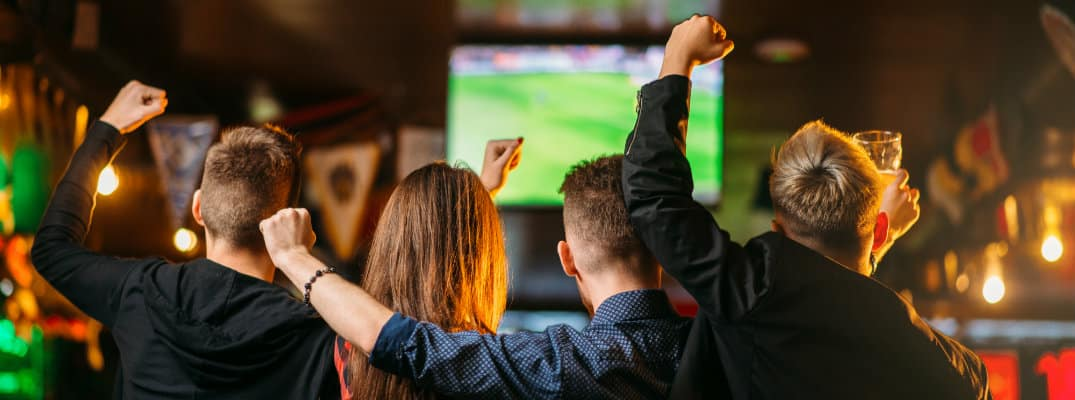 a group of friends huddle together at a sports bar with drinks as they cheer on their football team on the TV screen
