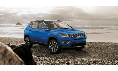 2019 Jeep Compass exterior shot with blue paint color parked on a rocky beach near a cloudy sky and sea
