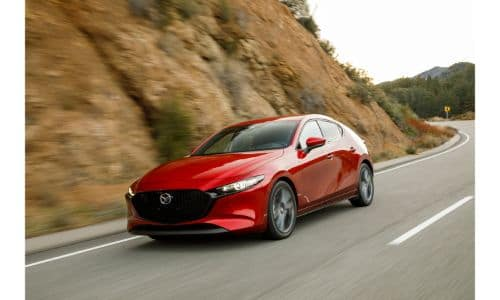2019 Mazda3 Hatchback exterior shot with red paint color driving by a mountain side