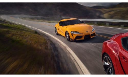 2020 Toyota GR Supra 3.0 Premium exterior shot with yellow paint color following another red GR Supra model