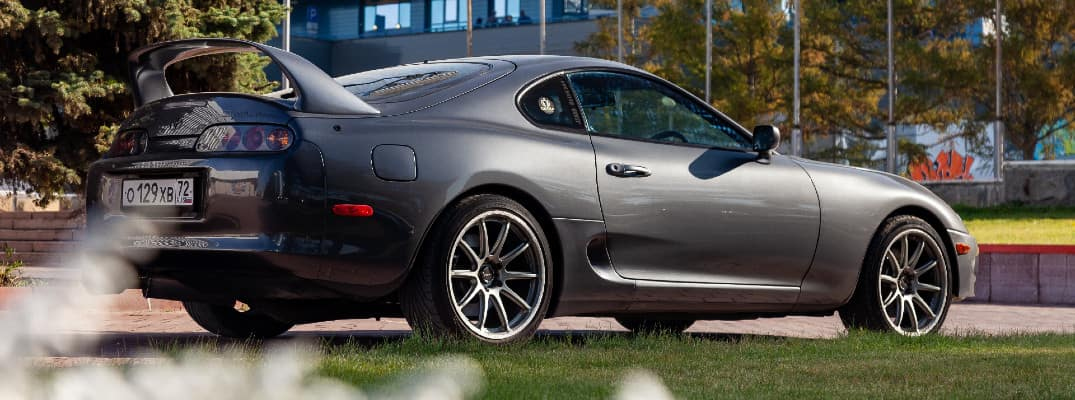 Toyota Supra coupe exterior side shot with gray metallic paint color and rear spoiler attachment