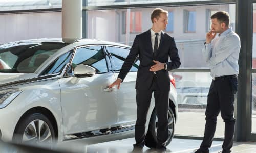 a salesman showing off a car to a customer at a car dealership