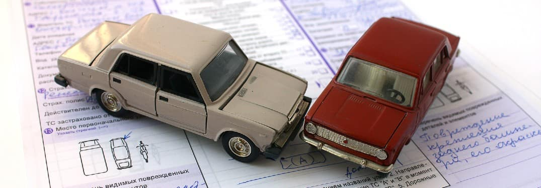 tiny car models in a collision on top of a car insurance policy term pamphlet