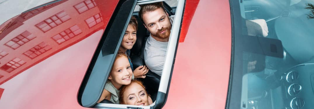 a family looking through a moonroof built into the roof of a red car