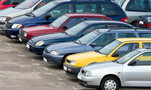 a used car lot with a line of different colored cars
