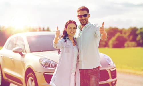 couple standing outside of car