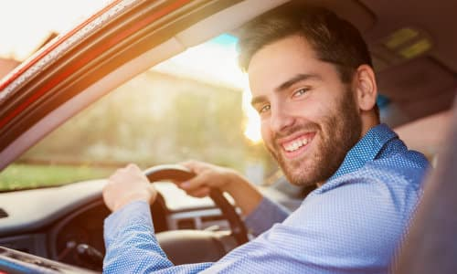 a smiling man in a blue dress shirt sitting in a driver's seat in a car as the sun glares