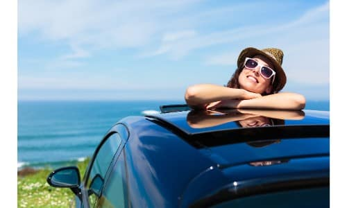woman relaxing on top of car through an open sunroof on a grassy hill by the water