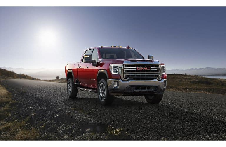 2020 GMC Sierra 2500HD exterior front shot with red paint color parked on an asphalt road with a cloudy sun behind it
