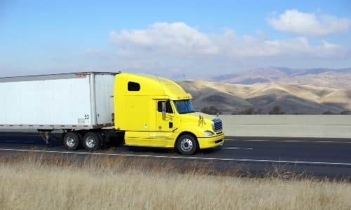 a bright yellow semi-truck driving through the open country with fields of dry grass on its sides