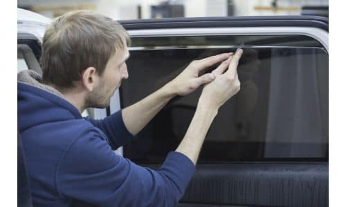 a car mechanic installing a tinted film to a car window