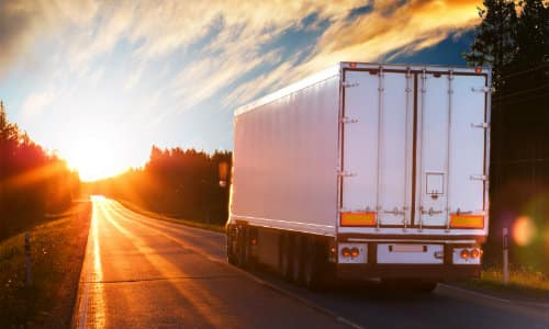 a white trailer and semi-truck hitch driving on a country highway road at sunset