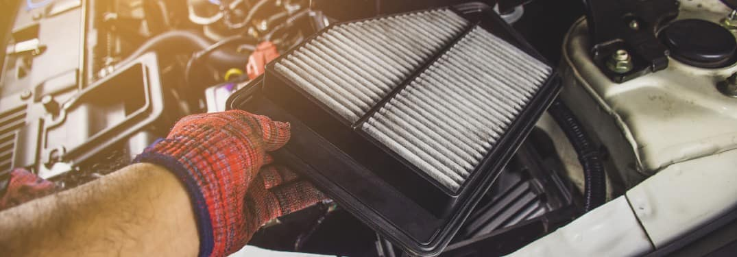 Car cabin air filter replacement being shown next to an open car hood by a service technician