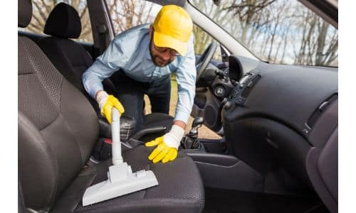 a man with a yellow hat and gloves vacuuming a vehicle's seating upholstery