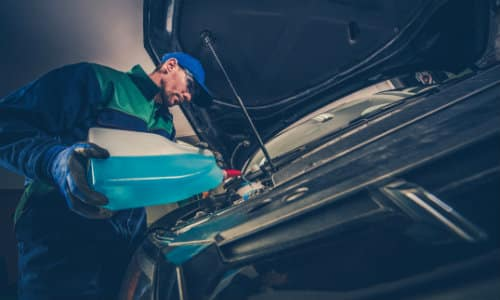 a mechanic in a green jumpsuit and blue hat adding neon coolant under a car hood