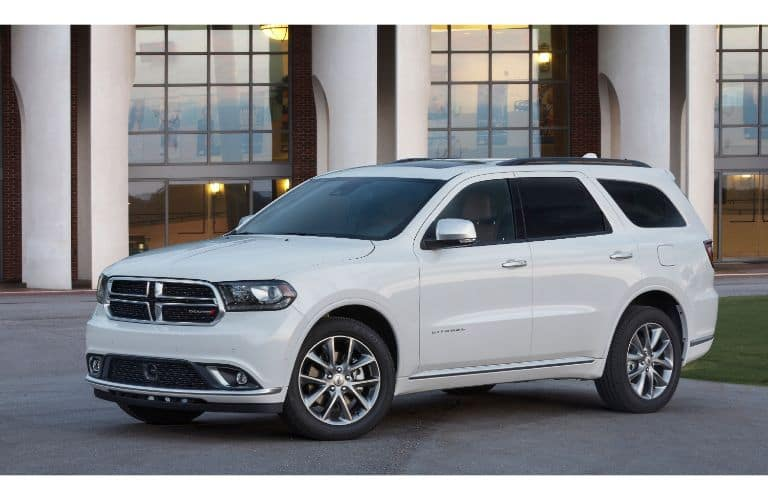 2020 Dodge Durango Citael exterior shot with white paint color and chrome accents parked in front of a building with glass frames and white pillars