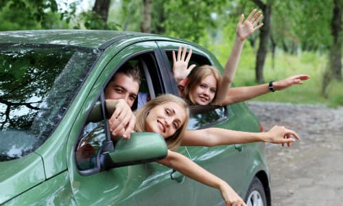 a family in a green SUV waving through the rolled down car windows