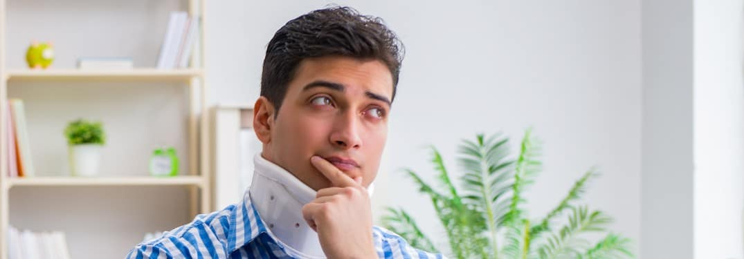 a young man sitting on a couch with a neck brace and thinking