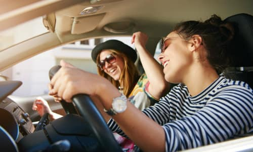 an interior shot of a car as a pair of friends dance and groove to music