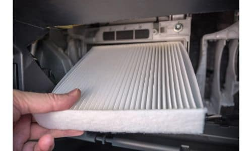 a hand replacing an air cabin filter