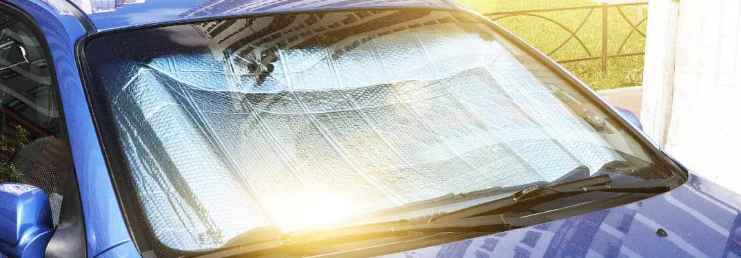 a protective reflective blanket place across the windshield of a blue car to absorb and reflect heat and sunlight