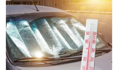a reflective sun shade place under the windshield inside a gray car with a thermometer graphic