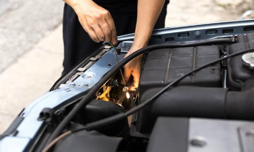 an auto mechanic fixing a headlight under the hood of a car