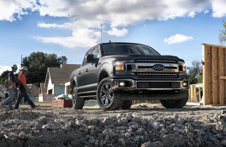 2020 Ford F-150 XLT SuperCrew exterior shot with gray metallic paint color parked on a construction worksite of gravel and rock