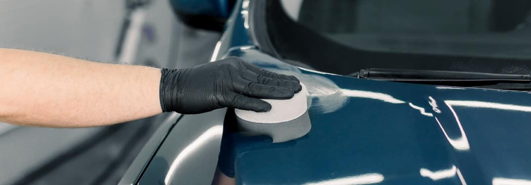 a gloved hand polishing the top of a blue car