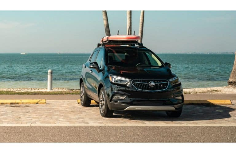 2020 Buick Encore exterior shot with loaded up roof rack parked by a beach and ocean