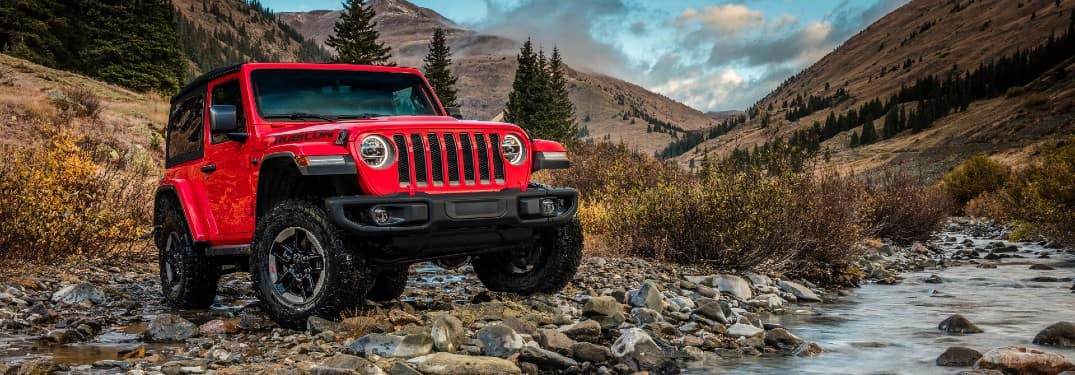 2020 Jeep Wrangler Rubicon exterior shot with Firecracker Red paint color parked on rocks next to a creek