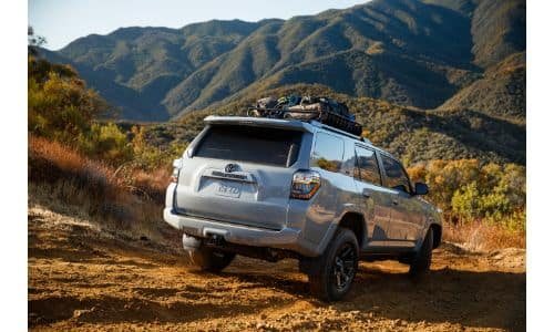 2021 Toyota 4Runner Trail Special Edition exterior rear shot with gray silver paint color driving on a rocky mountain plain trail