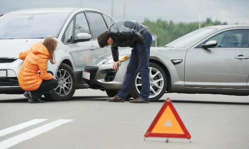 a man and woman examining a car collision in the middle of the road to inspect the accident damage