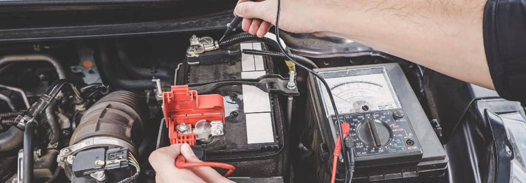 a service mechanic working on charging a car's battery under the hood