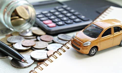 a small gold toy car set up next to a calculator, notebook, and jar of coins for calculating car financing