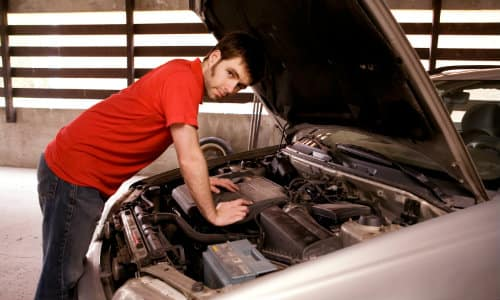 a man in a red t-shirt examining under the hood of his car in a garage
