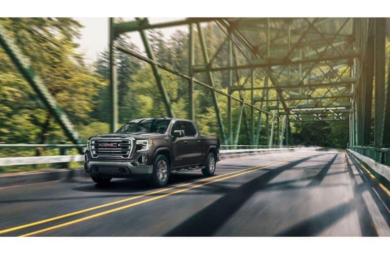 2020 GMC Sierra 1500 exterior shot driving across a bridge through a forest