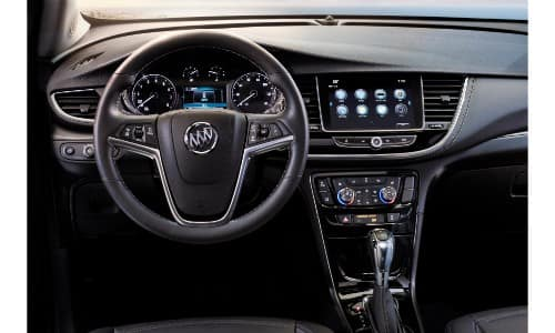 2019 Buick Encore interior shot of driver's seat view of steering wheel, dashboard screens, and transmission