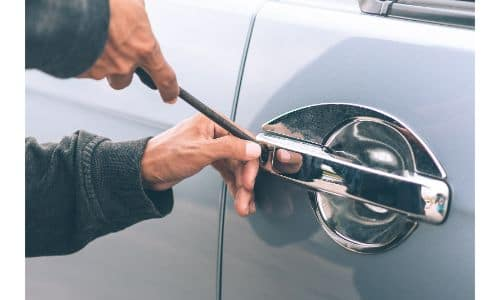 a thief breaking into a car by tinkering with a door handle