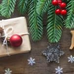 tree branches, fruit, snowflakes, presents, and more Christmas decorations on a wooden table